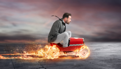 Man riding a mini car with flaming wheels signifying business development momentum.