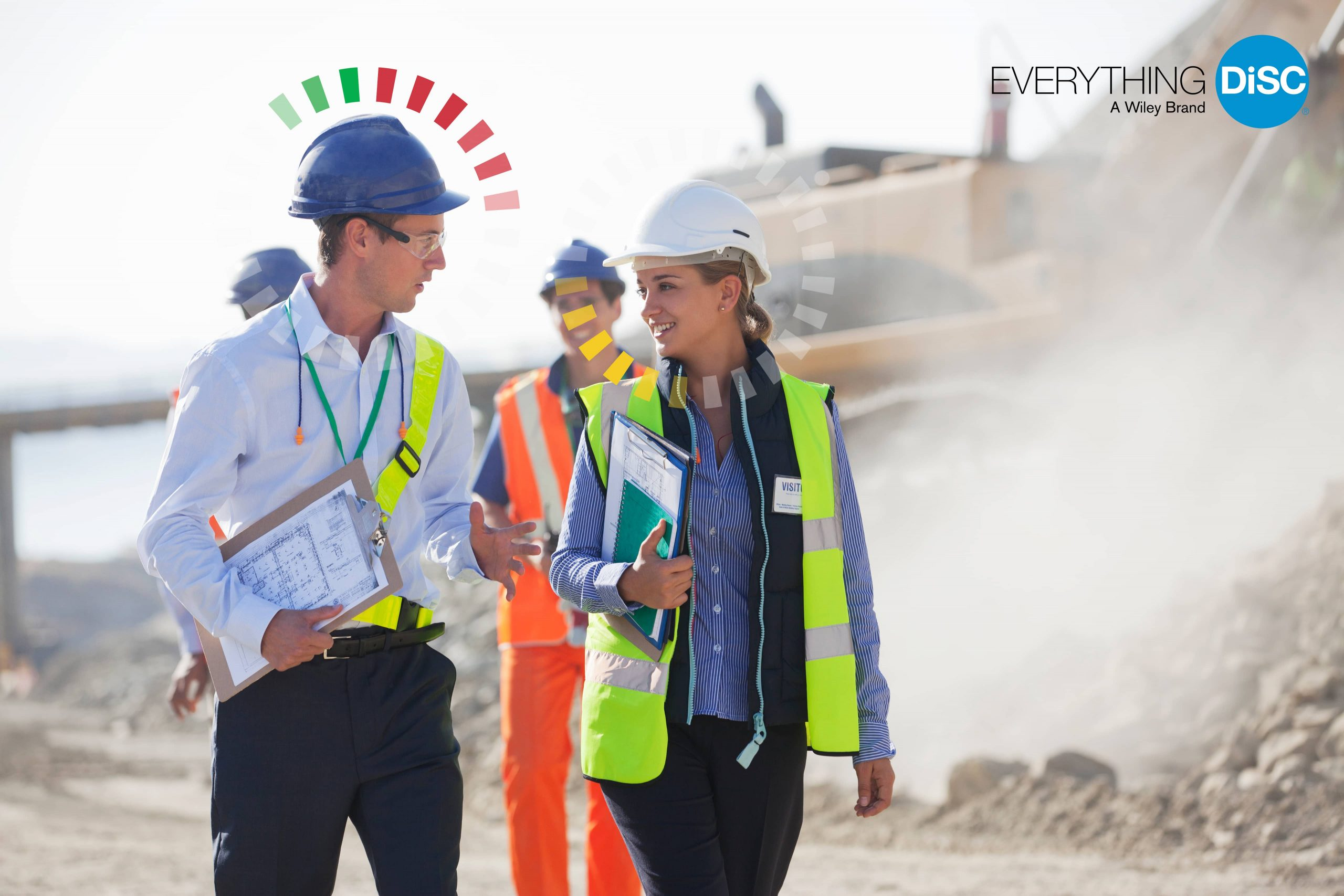 Male and female construction workers walking and talking.
