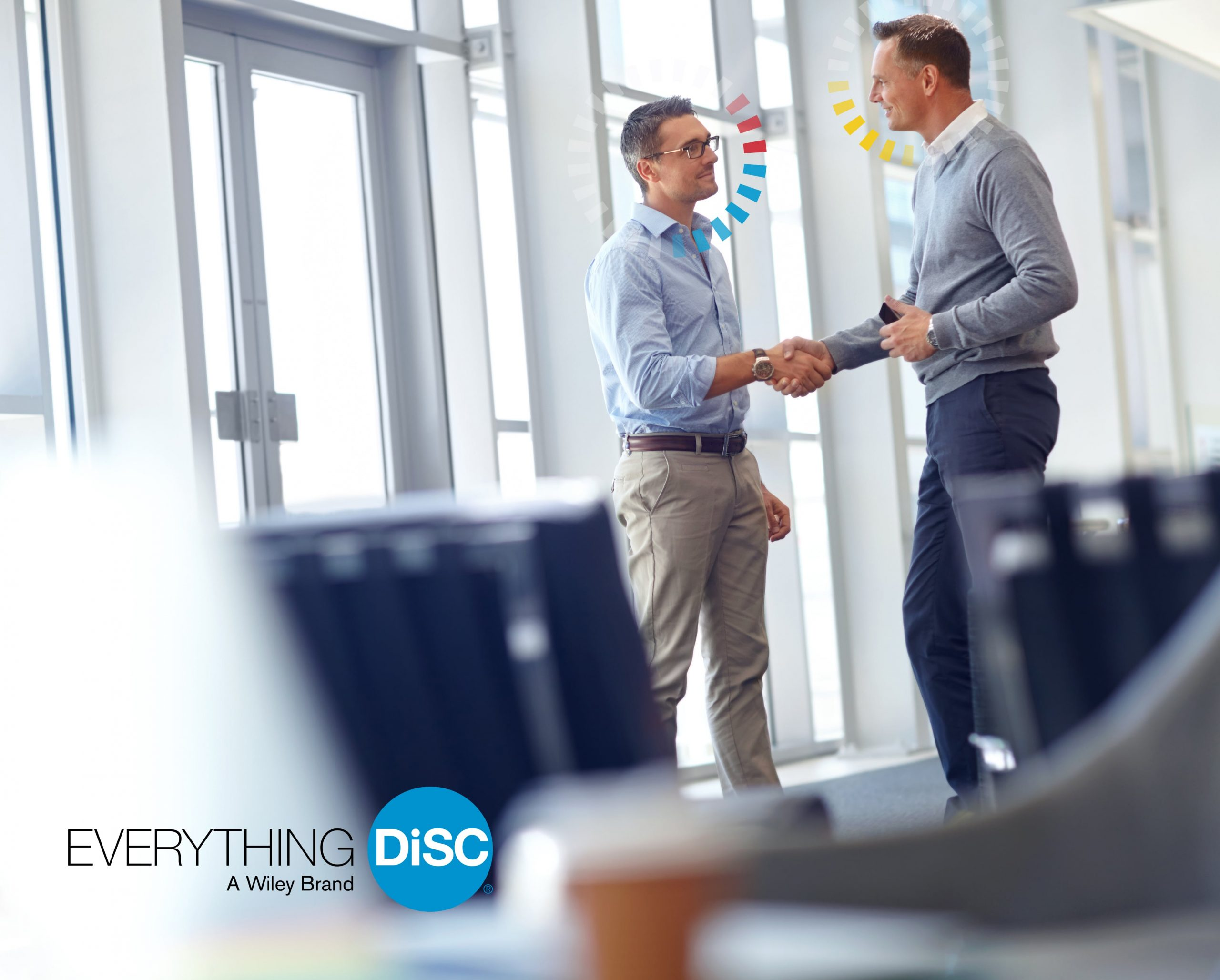 Two men standing and shaking hands inside a business office.