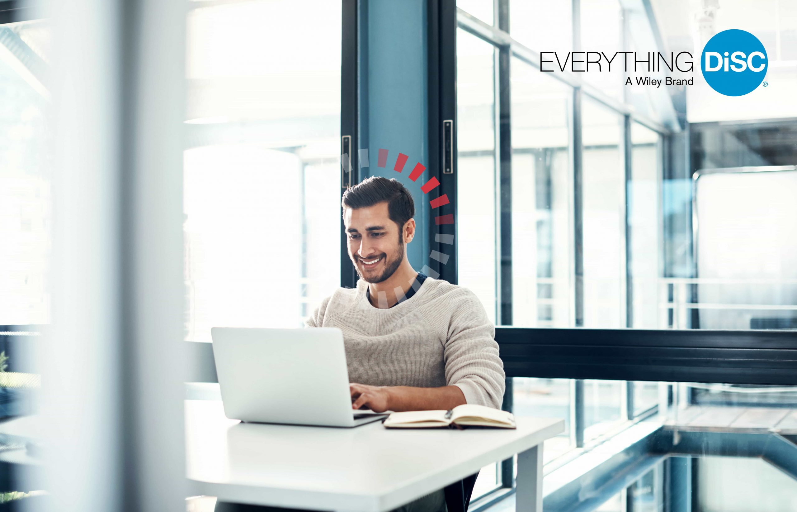 Salesperson sitting at desk looking at computer.